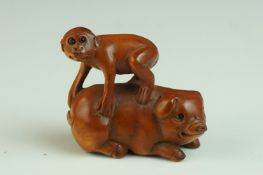 Japanese Carved Boxwood Netsuke in the form of a Monkey stood on a Pig, signed, 5cms long