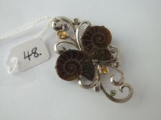 An unusual silver stone set brooch with 2 fossils