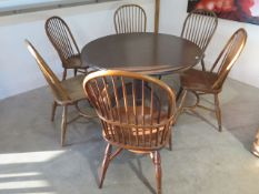 An oak tripod kitchen table with six ash and oak hoop back chairs, 74cm tall x 121cm diameter