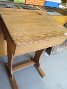 A pitch pine school desk with hinged lid and inkwell recess, 81cm high, 58cm wide, 47cm deep,