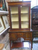 An Edwardian mahogany and line inlaid display cabinet, with glazed hinged doors enclosing two