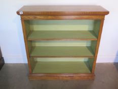 A burr oak open bookcase with two adjustable shelves and painted interior made by a local