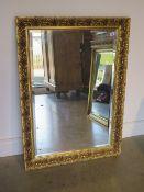 An ornate gilt mirror, 103cm x 75cm
