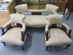 An Edwardian mahogany and upholstered salon suite comprising sofa and two armchairs, with cream