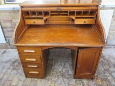 A 1930s oak rolltop twin pedestal four drawer desk with fitted interior, 117cm tall x 122cm wide x