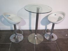 A glass top bar table, 91cm tall, with two moulded white seats gas lift stools, some usage marks but