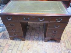 A mahogany effect twin pedestal eight drawer desk with an inset top, 79cm tall x 122cm x 61cm,