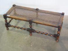 An oak barley twist cane seated stool, 28cm tall x 76cm x 31cm, caning good and a nice colour