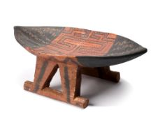 A Surinam stool South America with painted and scratch decoration, 21cm high, 58cm long.