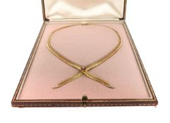 An 18ct gold collar necklace by Garrard & Co, set with a ruby and diamond flowerhead and diamond