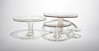 Three glass tazzae mid 18th century, in three sizes, with flat circular tops with galleried rims,
