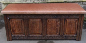 An 18th century oak coffer with panelled frame, moulded styles and carved foliate detail beneath a
