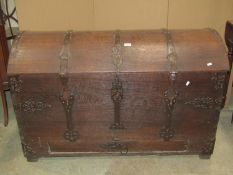An 18th century oak domed top trunk/coffer with exposed strap work hinges, lasps and fittings and