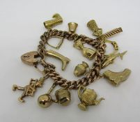 9ct curb link charm bracelet hung with sixteen novelty charms to include shark, peg, stirrup, 18ct