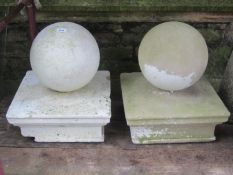 A pair of composition stone pier caps with sphere finials, the caps 43 cm square x 50 cm in height