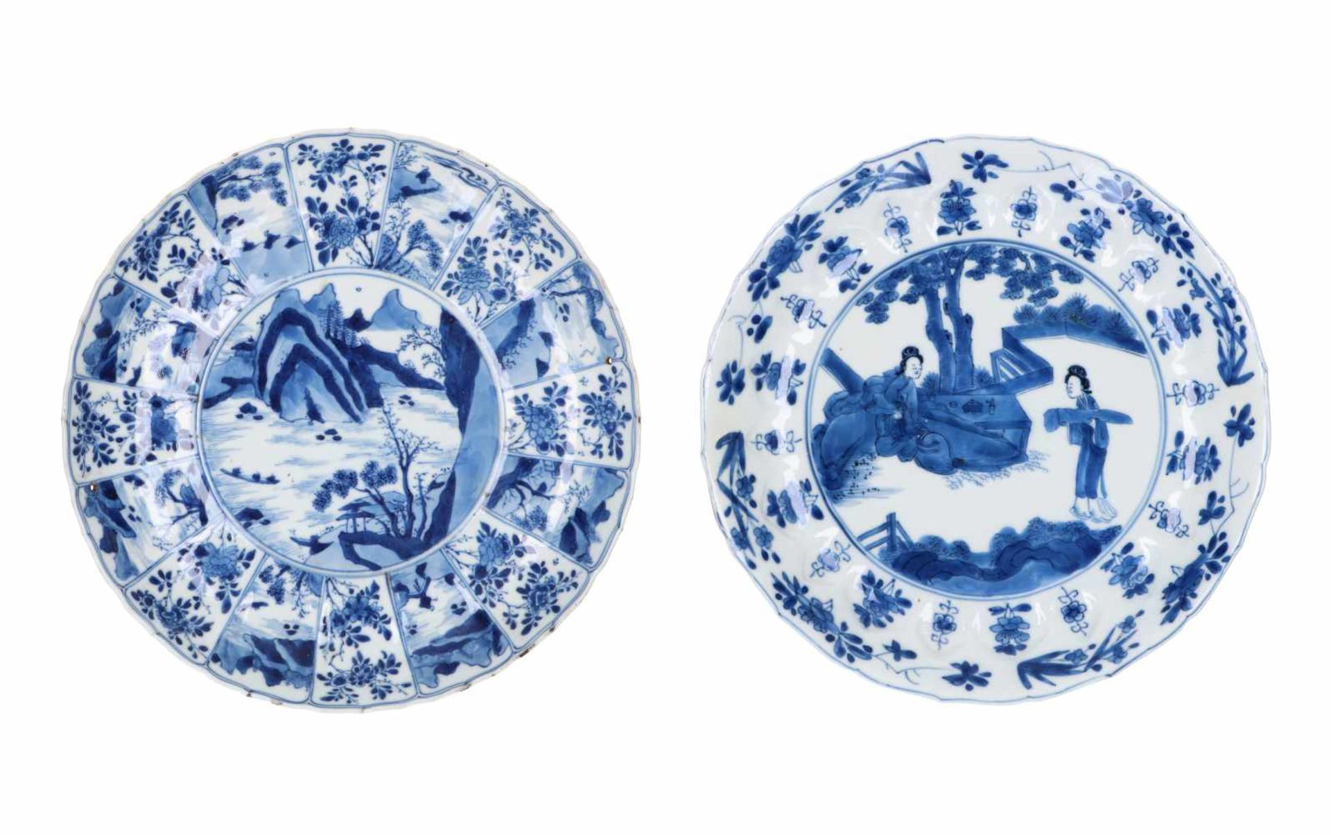 A blue and white porcelain dish with scalloped rim, decorated with ladies in a garden and flowers.