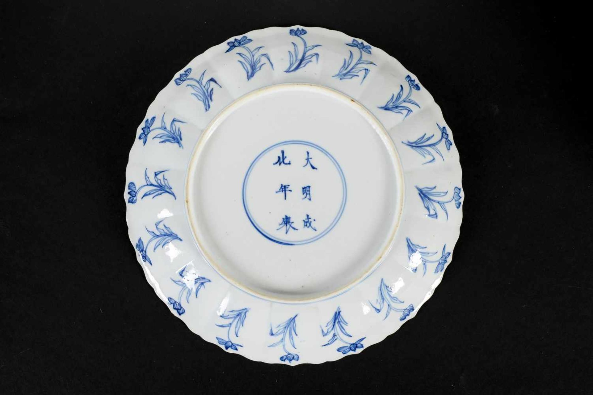 A lobed blue and white porcelain deep dish with scalloped rim, decorated with flowers and two long - Bild 2 aus 3