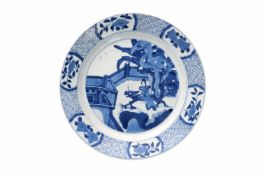 A blue and white porcelain dish, decorated with long Eliza on a bench in a garden. Marked with 6-