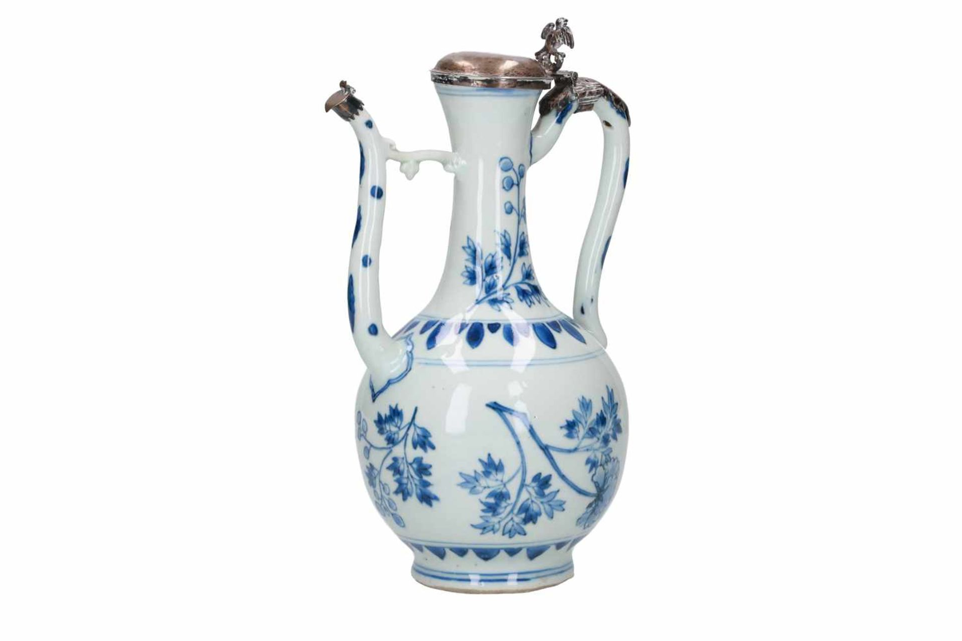 A blue and white porcelain jug with silver mounting, decorated with flowers and leaves. Unmarked.