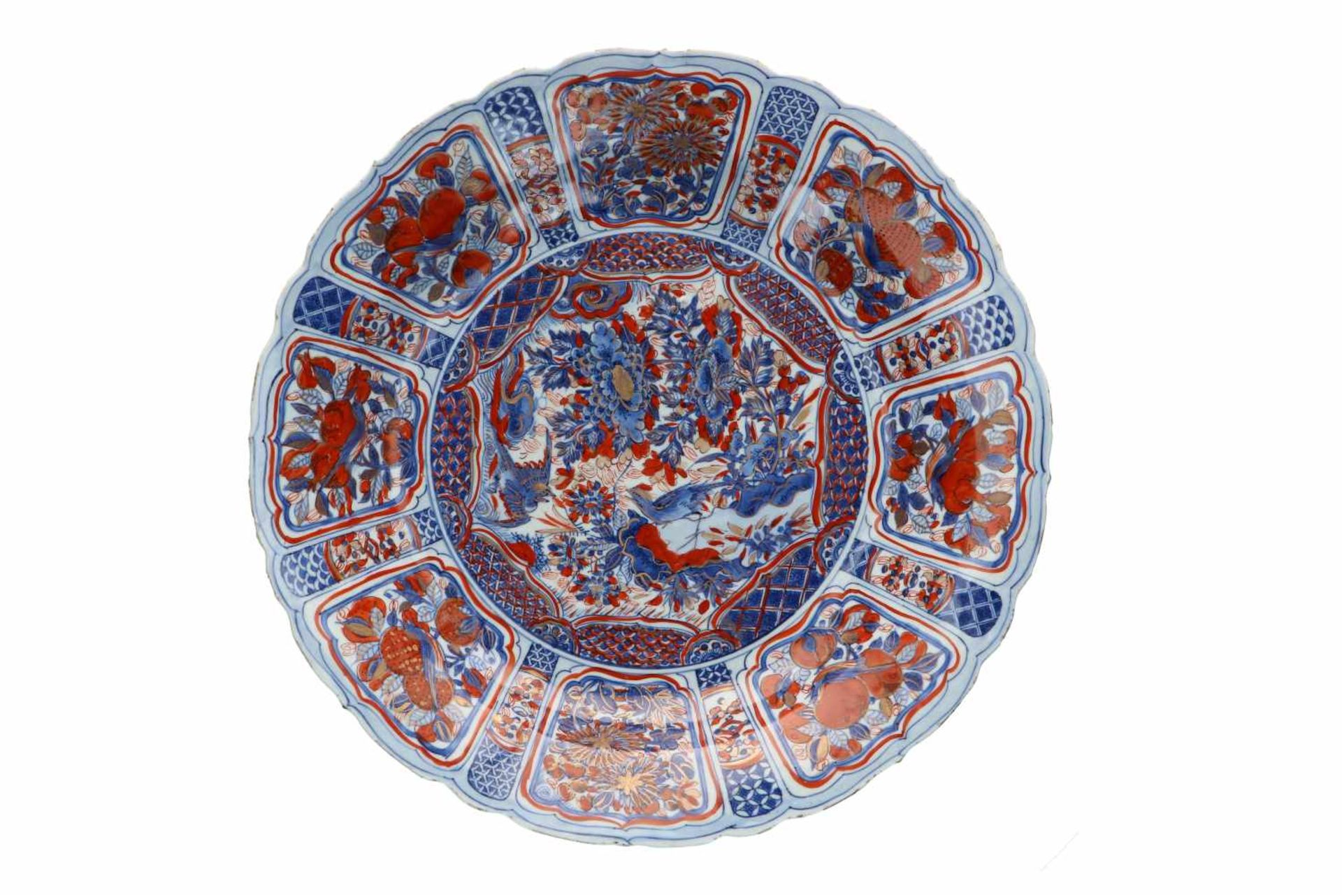 A blue and overglaze red porcelain deep charger with scalloped rim, decorated with flowers, fruits