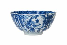 A blue and white porcelain bowl with scalloped rim, decorated with ladies in a garden and flowers.