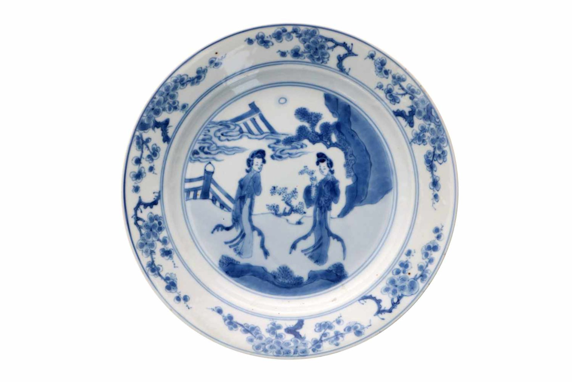 A blue and white porcelain deep dish, decorated with long Elizas in a garden and prunus flowers.