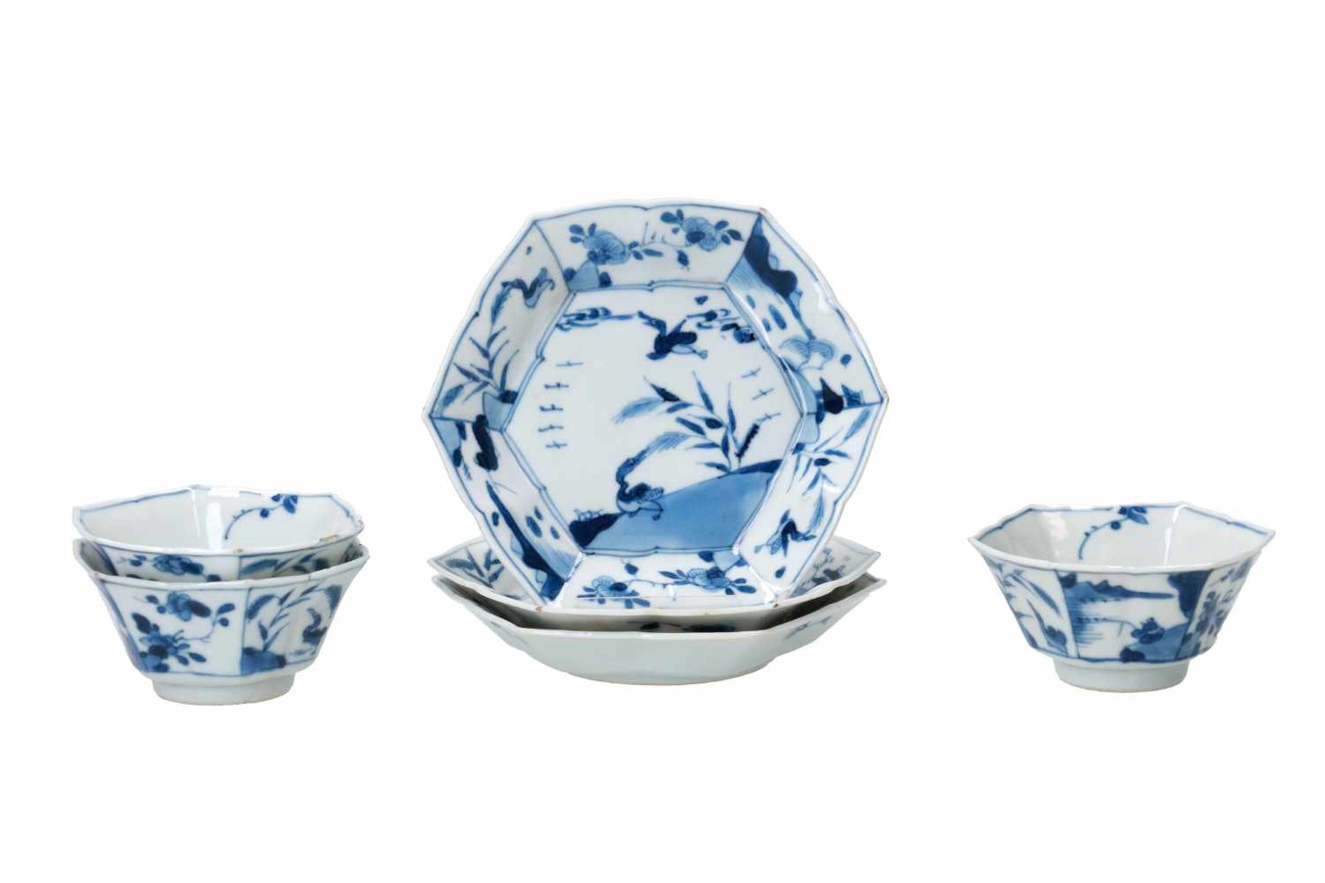 A set of three hexagonal blue and white porcelain cups with saucers, decorated with ducks, flowers