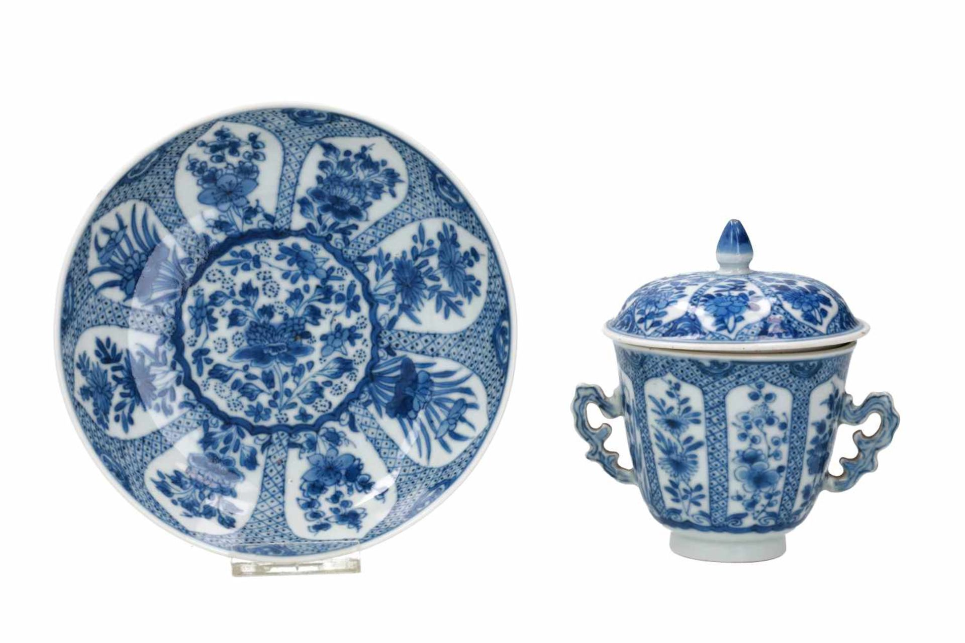 A blue and white porcelain lidded cup with two handles on a deep saucer, decorated with flowers.