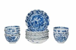 A set of nine blue and white porcelain cups with saucers, with scalloped rim, decorated with