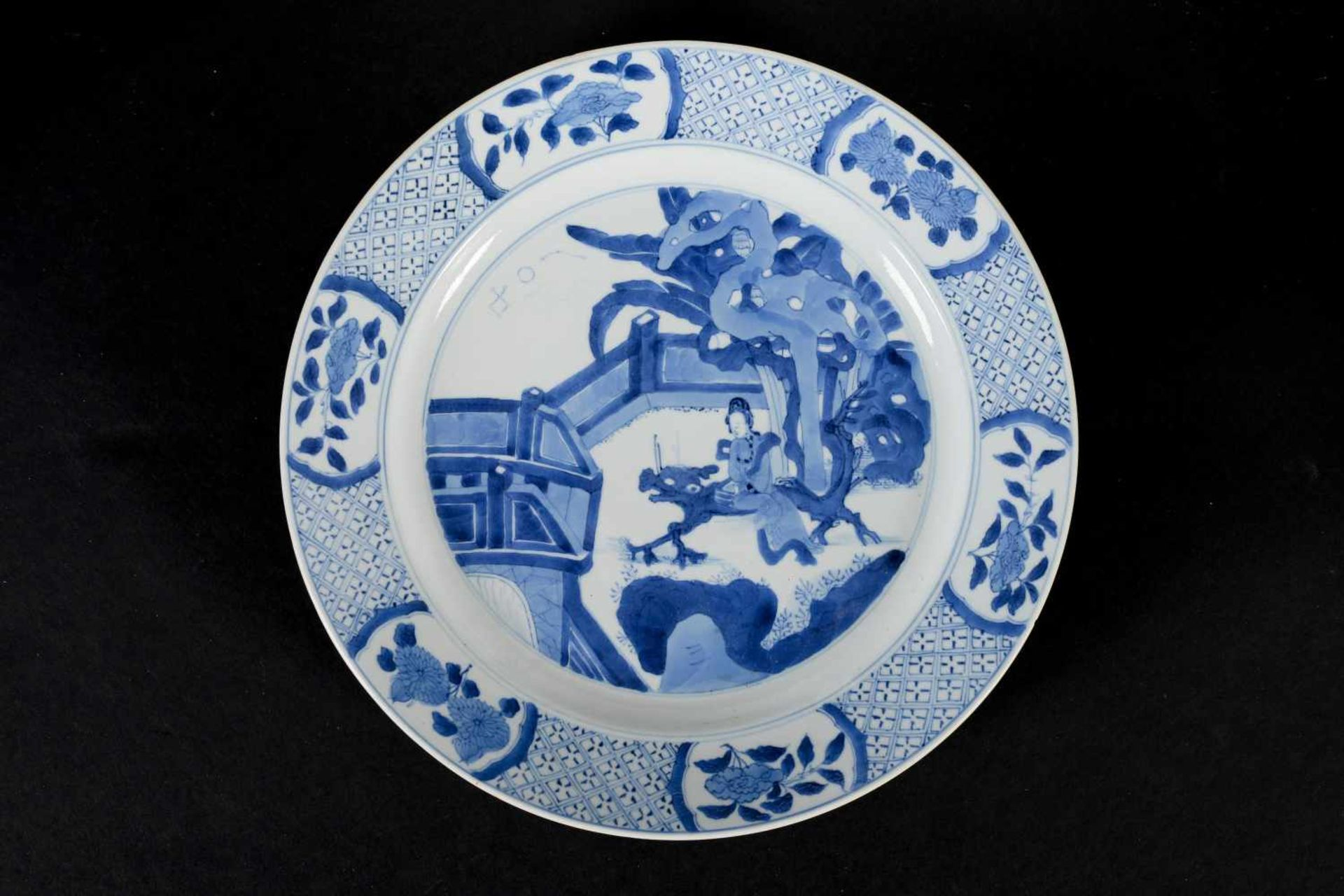 A blue and white porcelain dish, decorated with long Eliza on a bench in a garden. Marked with 6- - Bild 3 aus 3