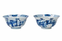 A pair of blue and white porcelain bowls, decorated with figures on a terrace, little boys and