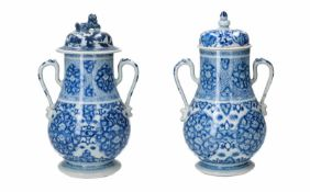 A pair of blue and white porcelain vases with two handles. Unmarked. Covers associated. China,
