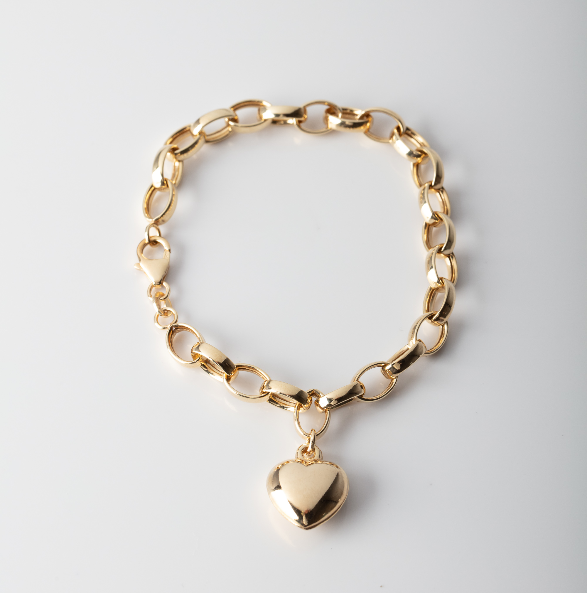 A 9CT GOLD & SILVER BONDED PUFF HEART BRACELET