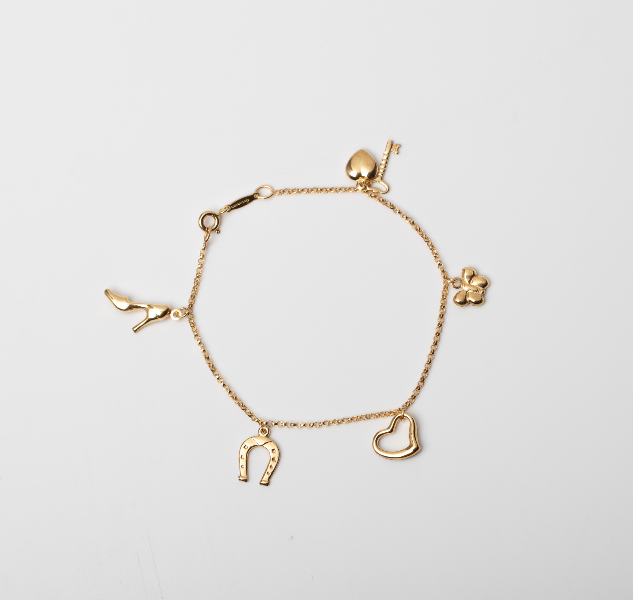 A 9CT GOLD & SILVER BONDED CHARM BRACELET