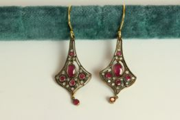 Pair of Ruby and Diamond flared drop earrings, each set with 6 rubies and 14 diamonds, approximate