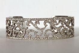 Brilliant cut diamond bangle, brilliant cut diamonds mounted across an open bangle, scrolling centre