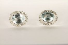 Pair of Aquamarine and Diamond Stud Earrings, set with a total of 2 oval cut light blue
