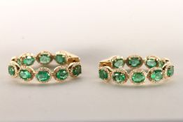 Pair of Emerald and Diamond Hoop Earrings, set with a total of 18 oval cut medium to dark green