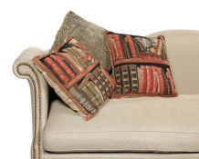 A pair of new tapestry style cushions of library books on shelves with a grey chenille cushion