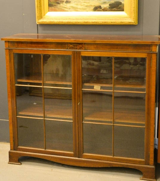 Lot 366 - An Edwardian mahogany glazed cabinet, with two doors enclosing two shelves, raised on bracket feet.