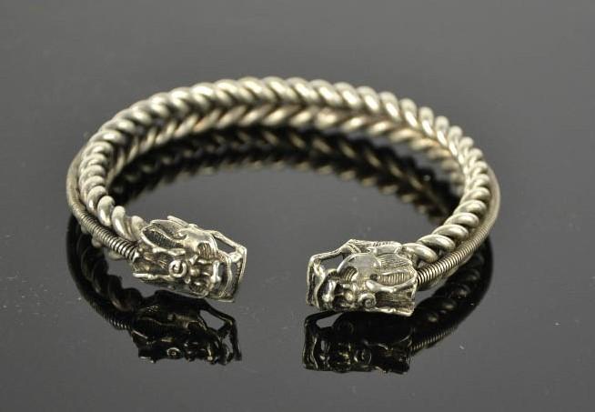 Lot 247 - A Tibetan Miao silver dragon bangle, coiled spine 44g. 7.5cm wide