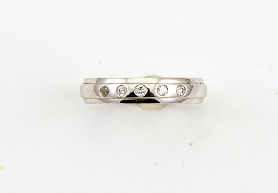 Lot 12 - A platinum and diamond band, marked 950, set with five brilliant cut diamonds, size N 4.6g.