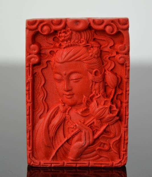 Lot 257 - A Chinese finely carved organic cinnebar pendant of 'Guanyin'