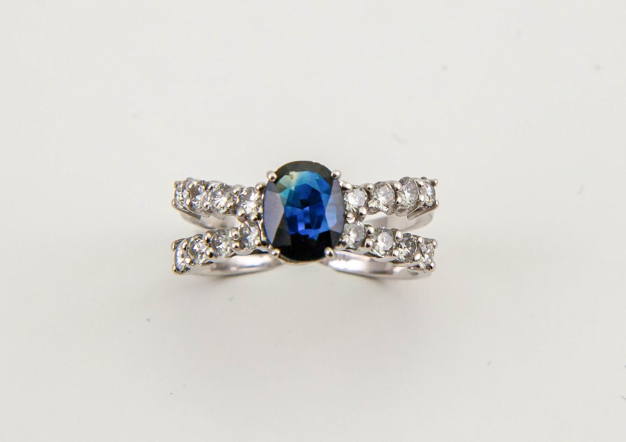 Lot 14a - An 18ct white gold, diamond and sapphire ring, the sapphire approx 1ct, centring a bow of diamonds