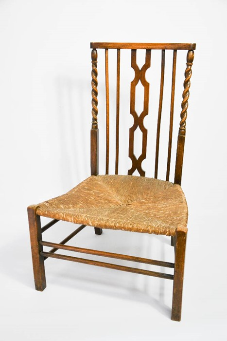Lot 359 - A 1930s prayer chair in oak, with rush seat and barleytwist supports.