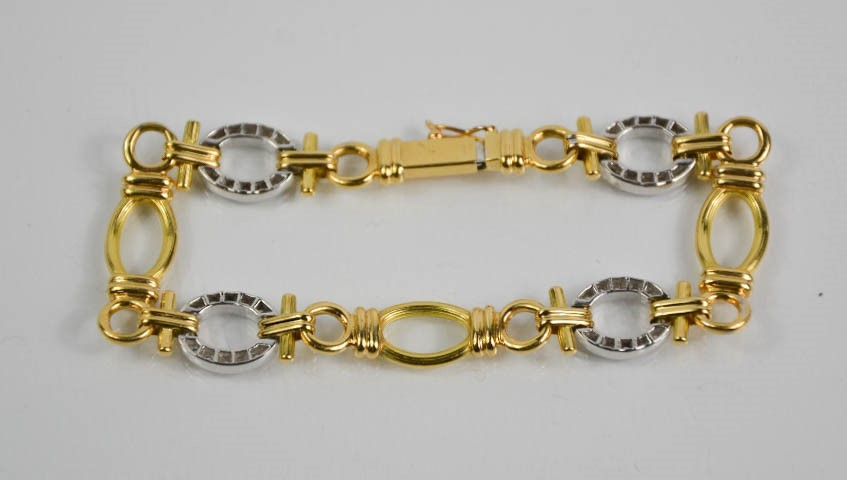 Lot 15 - A Boodles 18ct yellow and white gold bracelet, the white gold oval segments set with diamonds,