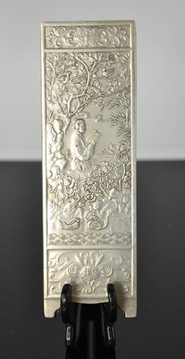 Lot 286 - A Tibetan Miao silver scroll weight depicting scholar reading in garden, signed and stamped 180gm