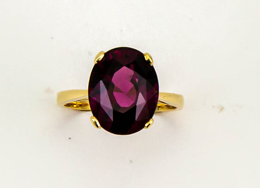 Lot 4 - A 9ct yellow gold and oval almandine garnet solitaire cocktail ring, the garnet approx 5.50ct,