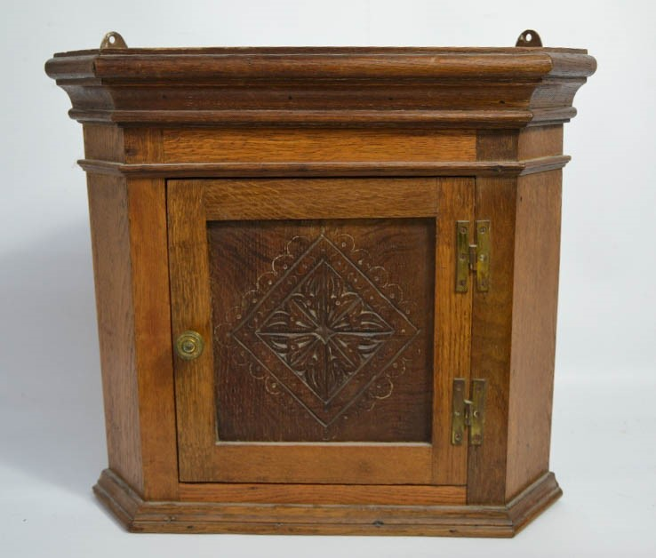 Lot 360 - A small oak corner cupboard, with carved door.