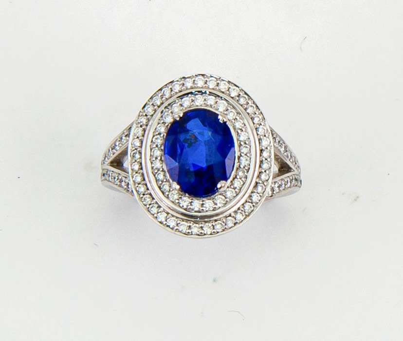 Lot 50 - An 18ct white gold, sapphire and diamond ring, the oval cut 2ct sapphire bordered by two rows of